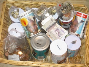 A basket stuffed with collection tins and cash.